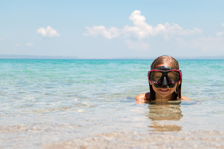 scuba mask: Beautiful young little girl with scuba mask enjoying in the sea. She is smiling and looking at camera.