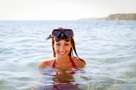 scuba mask: Beautiful young woman with scuba mask enjoying in the sea. She is smiling and looking away.
