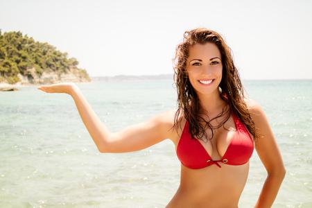 Hermosa mujer joven posando en bikini rojo en la playa. Ella está sonriendo y mirando a la cámara.