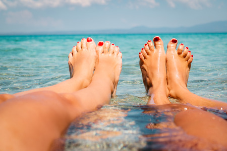 gay girl: Two girlfriends enjoying on the beach. They are lounging with legs in the sea. Close-up on the womans legs.