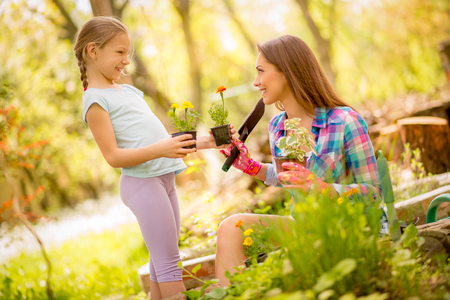 Cute little girl assisting her mother planting flowers in a backyard.