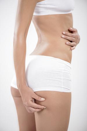 nalga: Primer plano de una mujer joven que controla las celulitis en su nalga.