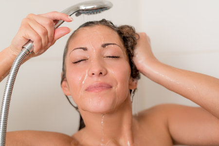 woman washing face: Beautiful young smiling woman washing face and hair while showering under shower head.