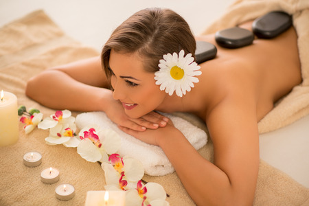 lastone therapy: Cute girl enjoying during a back massage with warm stones at a spa. Top view.