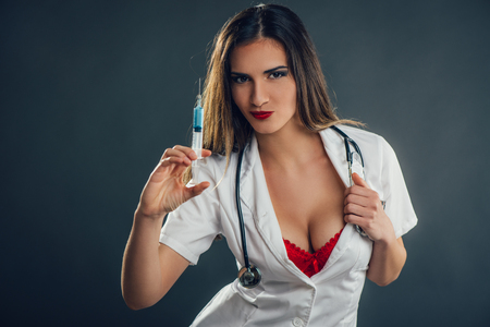 Portrait of a beautiful nurse holding injection. Looking at camera. Stock Photo
