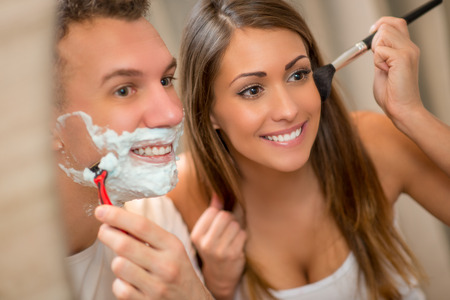 Portrait of a beautiful young happy couple having morning habits in front of their bathroom mirror. Man shaving and his girlfriend makeup. Selective focus.