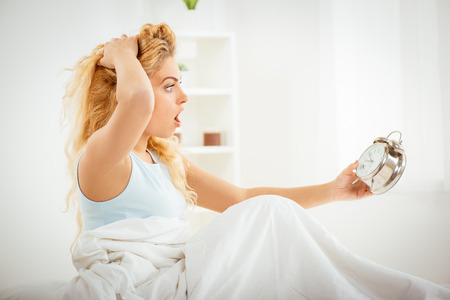 Cute young woman awakening in the morning. She is oversleep and looking with alarm clock.