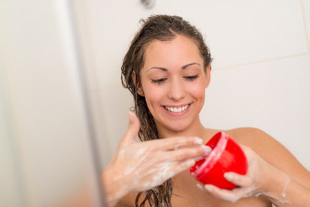 Beautiful smiling young woman washing her long hair. She is holding hydrating hair mask for repair her hair. Selective focus. Focus on girl. Archivio Fotografico
