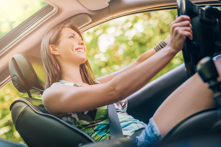 nice smile: Young beautiful girl with a nice smile driving a car.
