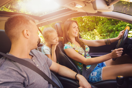 Beautiful family of three enjoying at driving a car and going on road trip. Archivio Fotografico