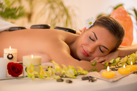 Cute woman enjoying during a back massage with warm stones at spa.