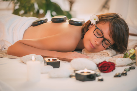 lastone: Beautiful woman enjoying during a back massage with warm stones at spa.