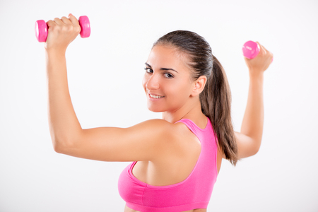 Beautiful girl doing exercise to strengthen shoulder with dumbbell. Looking at camera. White background. Stock Photo