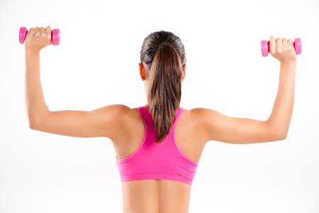 Young girl doing exercise to strengthen shoulder with dumbbell. Rear view. White background.