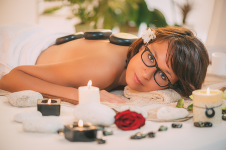 lastone therapy: Beautiful woman enjoying during a back massage with warm stones at spa. Looking at camera.