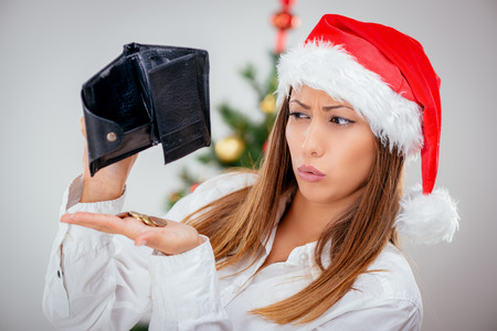 Young beautiful businesswoman wearing santa hat and looks worried at empty wallet.