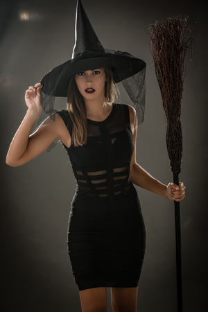 Young woman dressed like a witch. She is in dark clothing and holding a broom. Looking at camera. Stock Photo