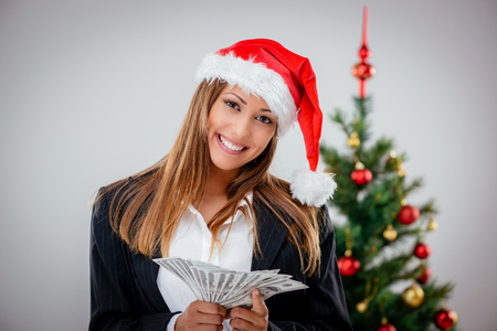 Successful businesswoman wearing santa hat and holding money. Looking at camera. Stock Photo