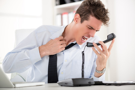 displeased businessman: Young angry business man sitting at the office and screaming on the phone.