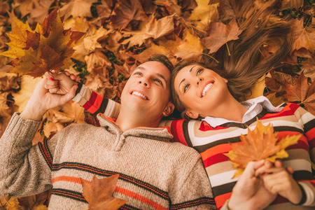 lying on leaves: Beautiful smiling couple enjoying in sunny forest in autumn colors. They are lying on the falls leaves. Stock Photo