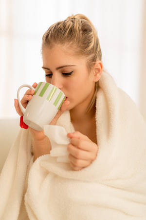 Beautiful illness girl sits tucked in a blanket and drinking tea.