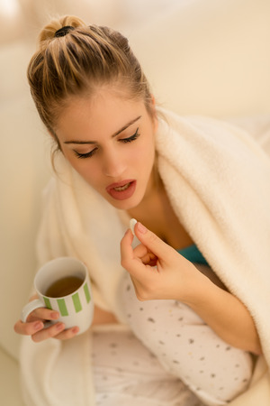 Beautiful young woman siting tucked in a blanket, holding a cup of tea and taking a pill.