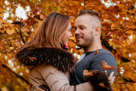 embraced: Portrait of a beautiful young couple in sunny forest in autumn colors. They are at embraced.
