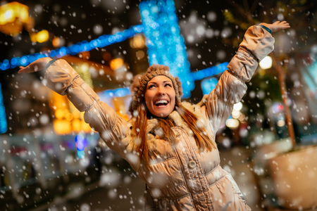 Cheerful beautiful young woman in warm clothing having fun while snowing in winter holiday time.
