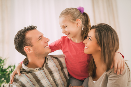 family  room: Beautiful young smiling family relaxing on sofa at living room. Stock Photo