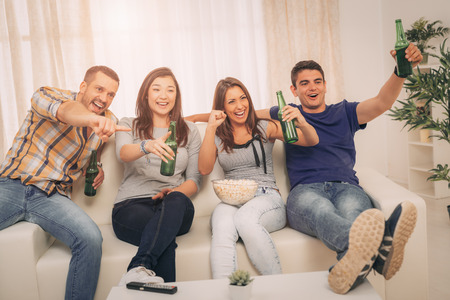 they are watching: Four cheerful friends hanging out in an apartment and watching a football game together. They cheering, drinking beer and eating popcorn.