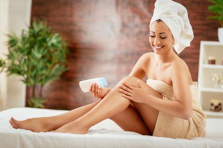 Beautiful young woman applying body lotion.  Zdjęcie Seryjne