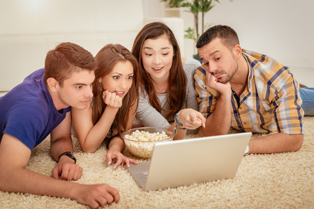 Four cheerful best friends having nice time in an apartment. They are watching movie together. Stock Photo