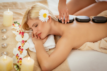Beautiful woman enjoying during a back massage with warm stones at a spa.