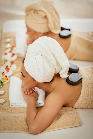 Two cute young women enjoying during a skin care treatment at a spa. Stock Photo