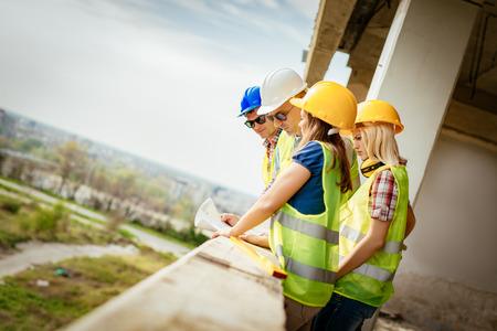Quatre architectes de construction plan d'examen sur un chantier de construction.