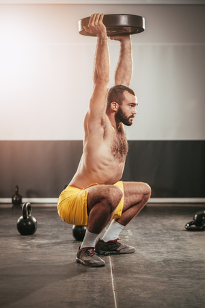 Young muscular man doing squats exercise with dumbbell. Strong male doing crossfit workout.