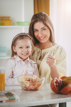 Mother and daughter having breakfast in the kitchen. They eating fruit salad.  Stock Photo