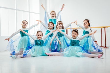 Smiling little girls in dresses practicing postures during ballet class. Looking at camera.