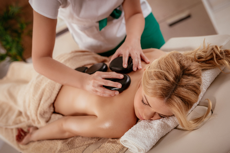 Beautiful woman enjoying during a back massage with warm stones at the spa.