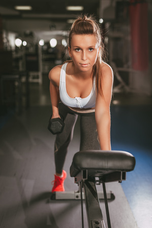 Beautiful young muscular woman doing exercise to strengthen her back at the gym. Looking at camera. Stock Photo