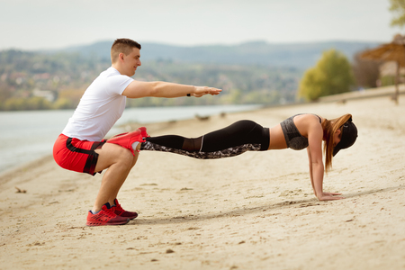 Young muscular couple having workout together on the beach. Handsome boy doing squats exercise, his cute girlfriend doing push-up. Stock Photo