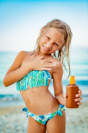 Cute little girl applying suntan lotion on the beach and looking at camera with smile on her face. Stock Photo