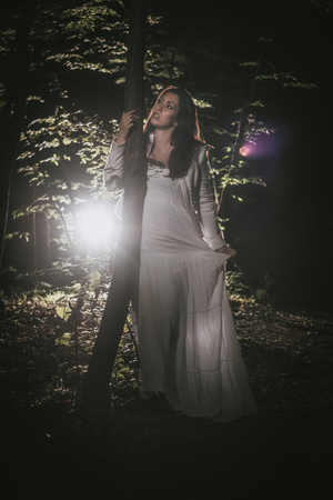 Young lonely woman walking through the forest at night in white dress.
