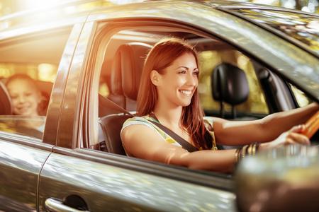 Giovane bella donna sorridente alla guida di un'auto. La sua carina figlia seduta sul retro e godendo. Archivio Fotografico - 76458616