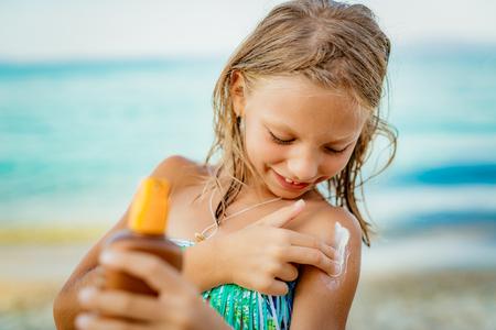 Cute smiling little girl applying suntan lotion on the beach.