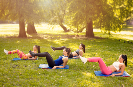 situp: Four beautiful female friends doing doing sit-up in the park.