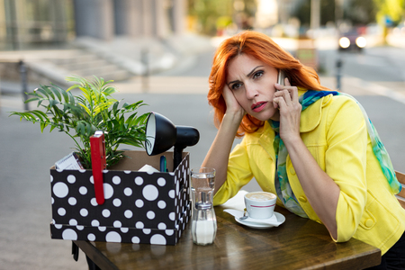 Serious pensive businesswoman sitting in a street cafe with a box full of things from the office when he fired and talking on smartphone. Stock Photo