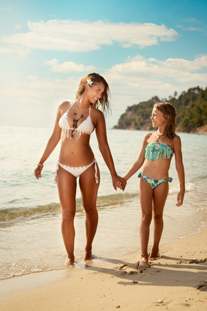 Beautiful little girl enjoying with her mother on the beach. She is walking by the sea and talking.