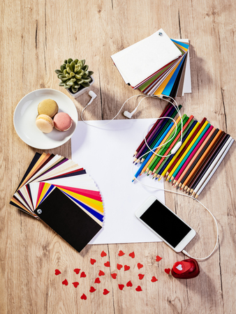 pallete: Top view of a designer workspace with blank paper and pallete color. Different office accessories, smartphone with blank screen and franch macaroons is on the table.