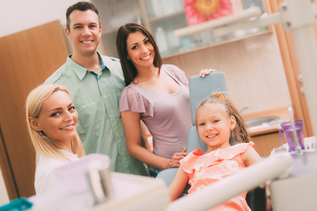 Happy young family at visit in the dentist office. They are  looking at camera. Stock Photo